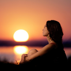 Young woman sitting on lake coast at sunset.