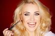 Laughing beautiful woman applying blusher