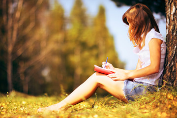 Young female student studying outdoors in the autumn.