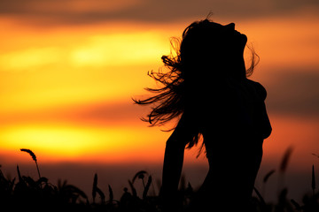 Young woman standing in dry field silhouette