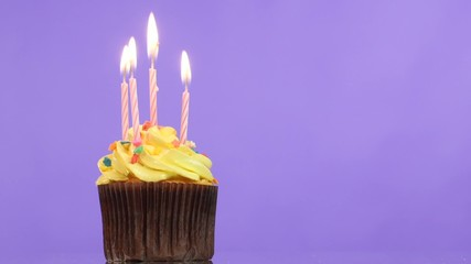 tasty birthday cupcake with candle, on purple background