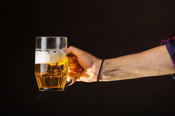 Male hand holding mug of beer