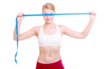 Fitness girl fit woman covering her eyes with measuring tape