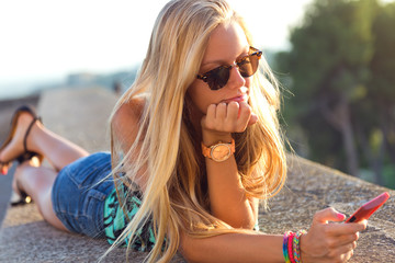 Beautiful blonde girl sitting on the roof with mobile phone.