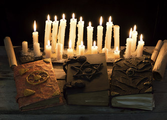 Three magic books with candles
