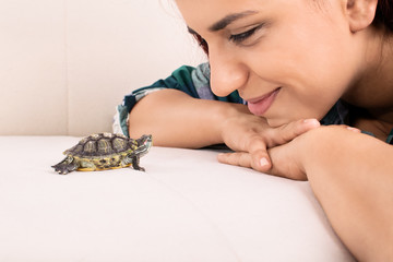 Young girl looking at a little turtle