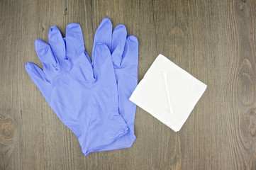 Purple latex gloves and cotton bud on tissue paper