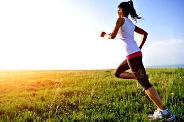Runner athlete running on sunset grass seaside