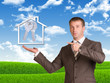 Business man hold house icon and metal keys in hand