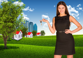 Woman holding key. Skyscrapers and houses with landscape