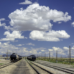 Puffy clouds over train cars