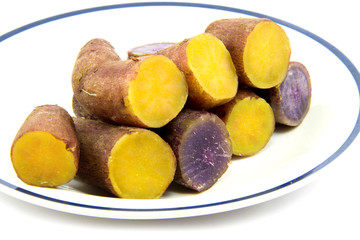 Boiled purple  and yellow yams line up in dish on white backgrou