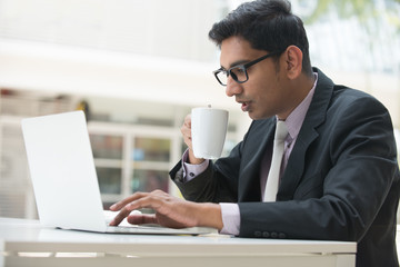 young indian business male on laptop and coffee at a cafe