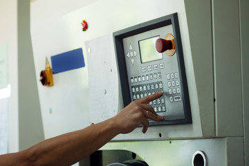 Man presses button on electronic control panel