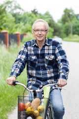 Smiling senior man riding a bicycle