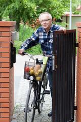 Senior man pushing bike through the gate