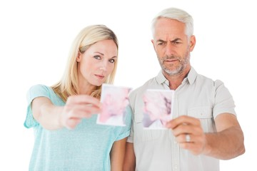 Unhappy couple holding two halves of torn photograph