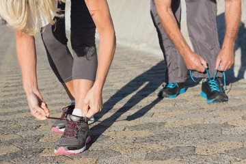 Couple tying their laces of running shoes