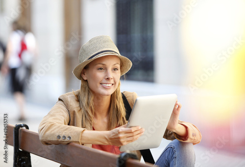 canvas print picture Trendy beautiful girl connected on internet in town