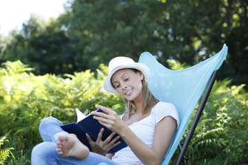 young woman reading book in outdoor chair