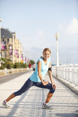 Cheerful jogger stretching after exercising in the street