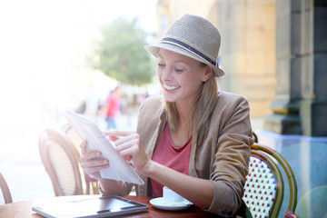Smiling girl in coffee shop reading newspaper