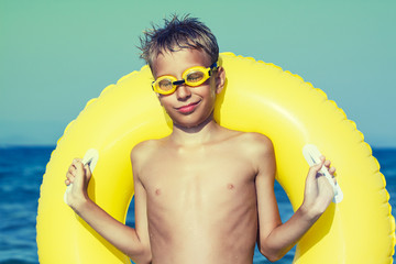 Funny chilld with swimmer goggles on beach with yellow float