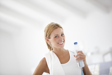 Fitness girl holding bottle of water after exercising