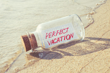 "Message in bottle ""Perfect vacation"" on beach."