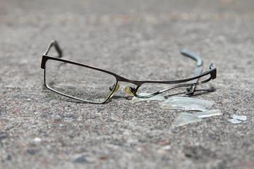 broken eyeglasses on concrete