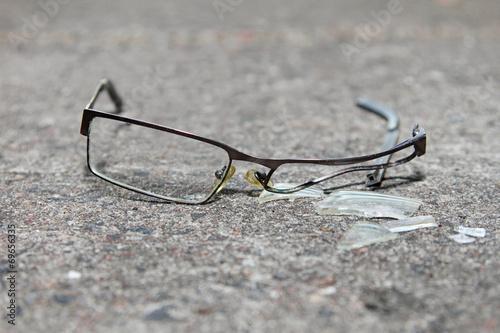 broken eyeglasses on concrete - 69656335