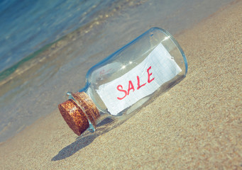 "Message in bottle ""Sale"" on beach. Creative marketing concept."