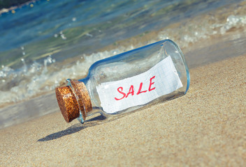"Message in a vintage bottle ""Sale"" on beach."