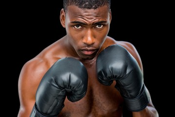 Portrait of shirtless muscular boxer in defensive stance