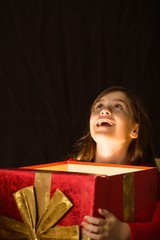 Little girl opening a magical christmas gift