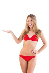 Fit blonde in red bikini presenting with hand