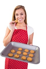 Pretty homemaker showing hot cookies