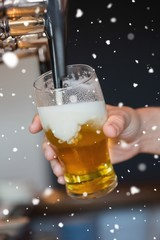 Composite image of hand holding glass filling beer
