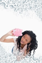 Composite image of woman looking inside her piggy bank