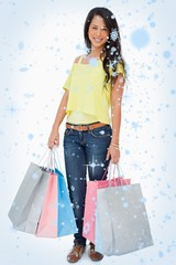 Composite image of beautiful woman student with shopping bags