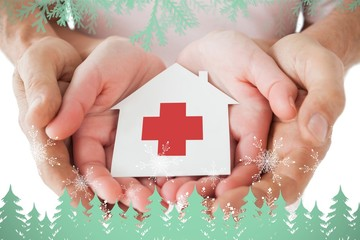 couple holding paper house with red cross
