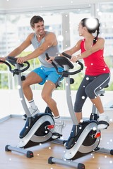 Smiling young couple working out at spinning