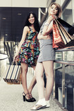 Two young fashion women with shopping bags in the mall