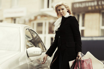 Young fashion woman with shopping bags on the car parking