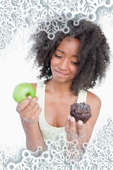Woman hesitating between a muffin and an apple