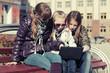 Teenage school girls using laptop on the bench