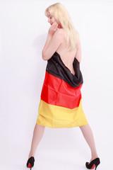 Nackte Frau von hinten, eingehüllt in eine Deutschland Fahne