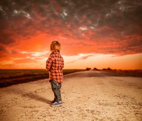 little boy at rural road sunset