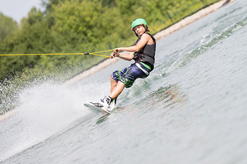 Junger Mann beim Wakeboarden Wassersport