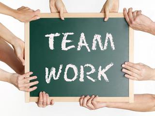 Many hands display a blackboard with teamwork